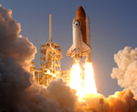 Space shuttle launching from ground pad