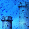 Open vertical stacks at an industrial plant with condensation droplets overlay